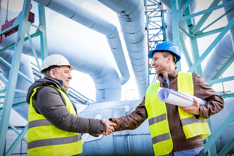 Photo of two construction workers wearing hard hats shaking hands in agreement